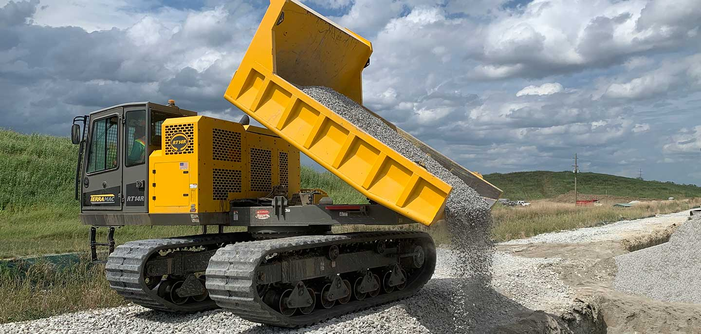 government equipment RT14R crawler carrier spreading stones along a road